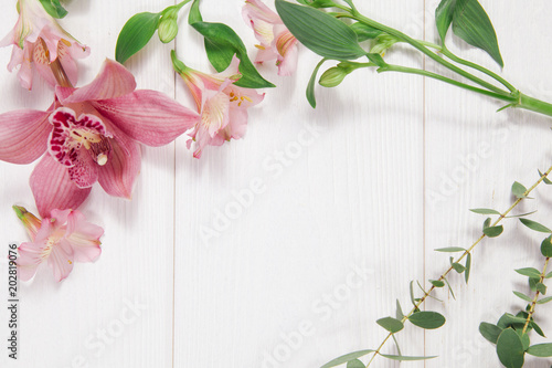 Foto op Canvas Bloemen Frame with flowers on white wooden background. Concept