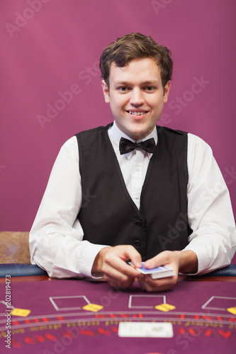 Dealer holding cards in a casino плакат