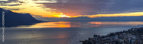 Scenic view of sunset over the Leman lake with yellow sky with clouds and Alps mountains in background, Montreux, Switzerland Wallpaper Mural