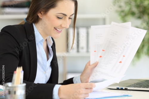 Happy executive managing different documents at office Canvas Print
