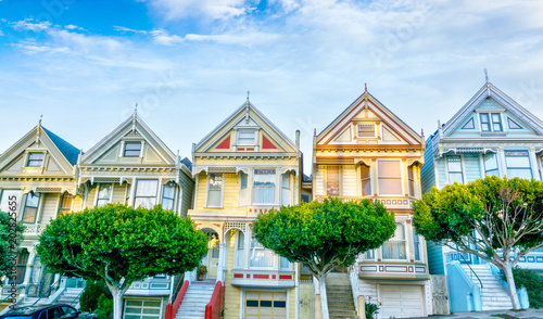 Late afternoon sun light up a row of colorful Victorian houses known as Painted Ladies across from Alamo Square. The historic houses were built between 1892 and 1896.