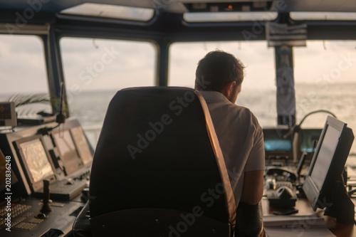 Fotografia  Oficer nawigacji pokładowej na mostku nawigacyjnym