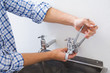 Plumber hands fixing water tap with pliers
