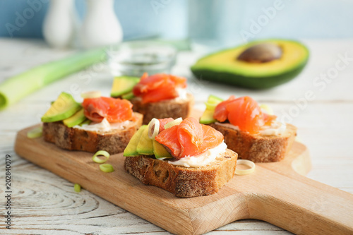 Photo sur Toile Entree Tasty sandwiches with fresh sliced salmon fillet and avocado on wooden board, closeup