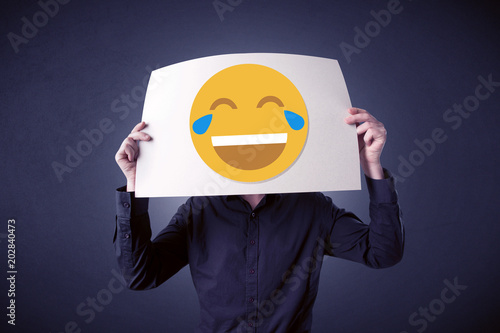 Staande foto Vlees Young businessman hiding behind a laughing emoticon on cardboard