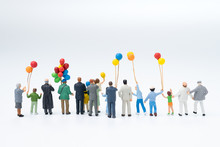 Back View Of Miniature People Happy Family, Audiences, Spectators Holding Balloons Watching The Show With White Background, Love, Family Day, Festival Or Interesting Event Concept