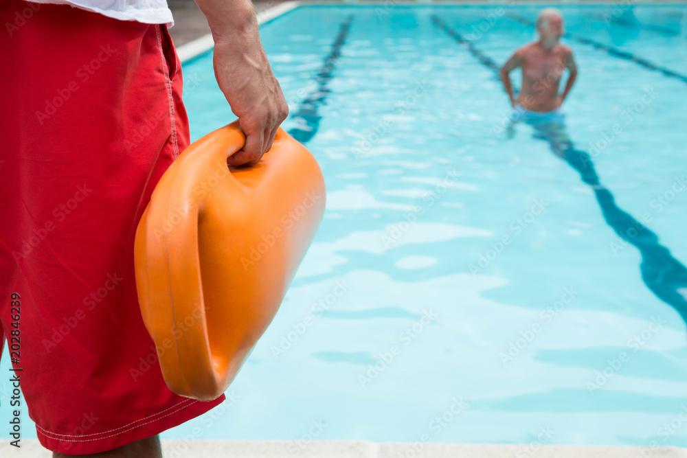 Fototapeta Lifeguard holding rescue buoy at poolside
