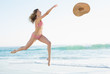 Joyful young woman jumping on beach