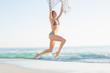 Joyful slender woman jumping in the air holding shawl