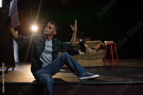 Actors reading their scripts on stage Canvas Print