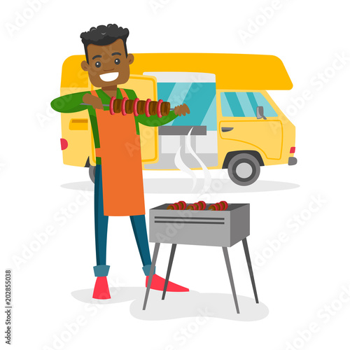 Young African American Man Preparing Meat On Grill On The Background
