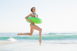 Gorgeous young woman holding a rubber ring while jumping on beach