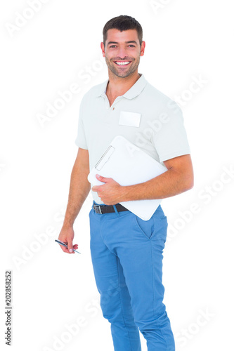 Fotografía  Smiling male handyman with clipboard and pen on white background