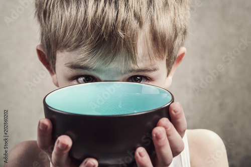 Foto Child holding an empty bowl, hunger concept