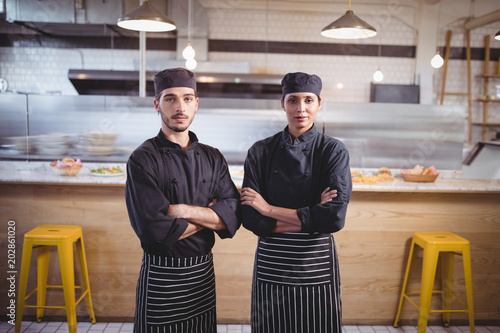 Portrait of confident young wait staff in black uniform standing with arms crossed at coffee shop