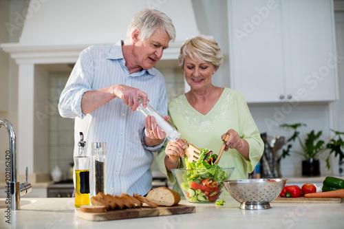Fotografía  Happy senior couple preparing vegetable salad