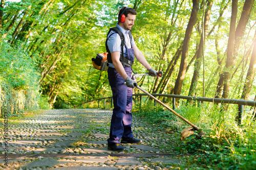 Fotografija Professional gardener using an lawntrimmer in garden