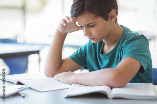 Foto Attentive schoolboy studying in classroom