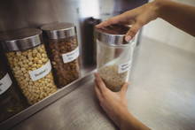 Female Chef Selecting A Spice Jar In The Commercial Kitchen