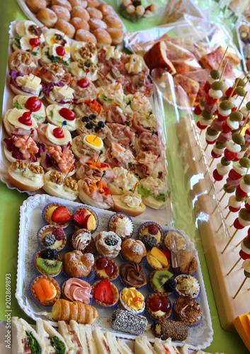 Tuinposter Buffet, Bar buffet with many trays filled with sweet pastries and sandwiches