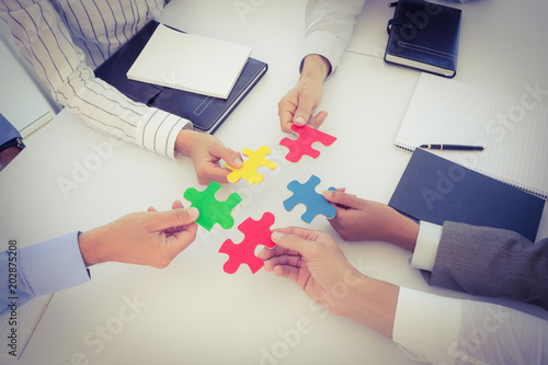 Fototapety, obrazy: Business colleagues holding piece of puzzle