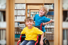 Happy Boy Pushing Friend On Wheelchair Against Library