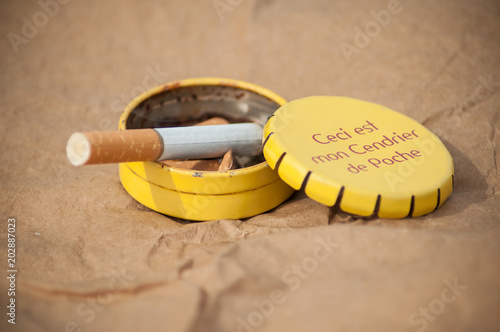 closeup of metallic pocket ashtray with texte in french on brown background thi Wallpaper Mural