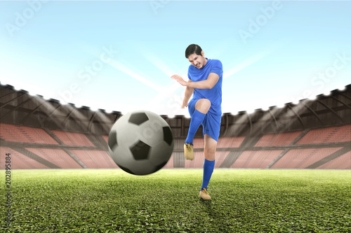 Fotobehang Voetbal Handsome asian soccer player practicing with the ball