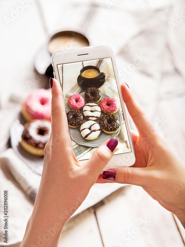 Woman photographing breakfast with coffee and donuts. Taking food photo with mobile phone.