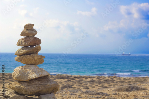 Foto op Plexiglas Cyprus Stones pyramid on background of Mediterranean sea. Seashore background with pile of stones. Tombs of Kings necropolis in Paphos, Cyprus