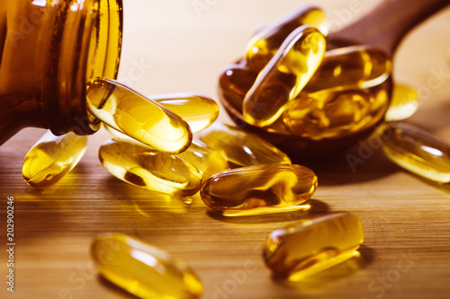 Fototapeta Close up the vitamin D and Omega 3 fish oil capsules supplement on wooden plate for good brain , heart and health eating benefit obraz
