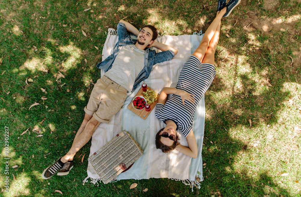 Fototapety, obrazy: Couple relaxing on a picnic at park