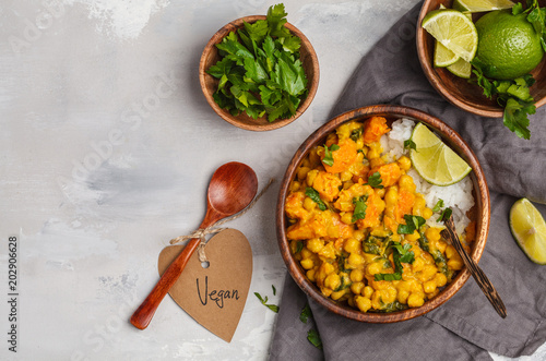 Vászonkép  Vegan Sweet Potato Chickpea curry in wooden bowl on a light background, top view