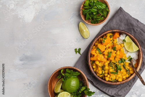 Valokuva  Vegan Sweet Potato Chickpea curry in wooden bowl on a light background, top view