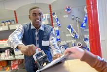 Hardware Store Employee Applying Stamp On Document