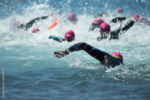 Valokuva  Group people in wetsuit swimming at triathlon