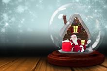 Santa Sitting In Snow Globe Against Shimmering Light Design Over Boards