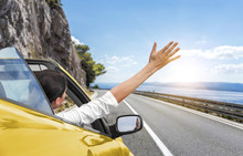 A Young Woman Is Driving By Car To The Sea And Waving Her Hand From A Yellow Convertible Car. Vacation On The Sea Coast.