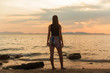 Young fit sexy girl in standing on a beach during sunrise or sunset in front of a calm sea, showing back to the camera.