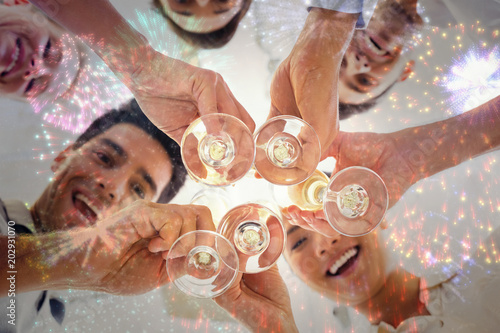 Fotografia  Casual business team toasting with champagne against colourful fireworks explodi