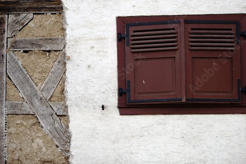 Fotografie, Obraz  Fensterluke in der Scheune / Eine markante Fensterluke aus Holz in einer Scheunenwand mit abblätternder Putzschicht