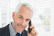 Closeup of smiling mature businessman using cellphone