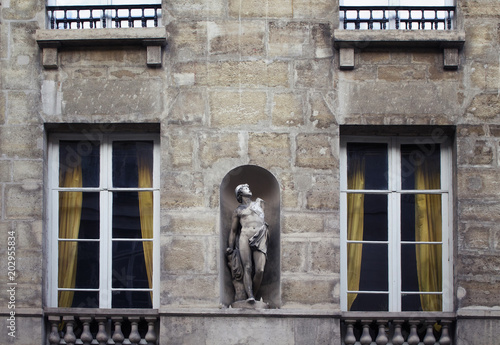 View of a statue / sculpture placed on the facade of a building in Saint-Germain area of Paris showing French / Parisian architectural style Poster