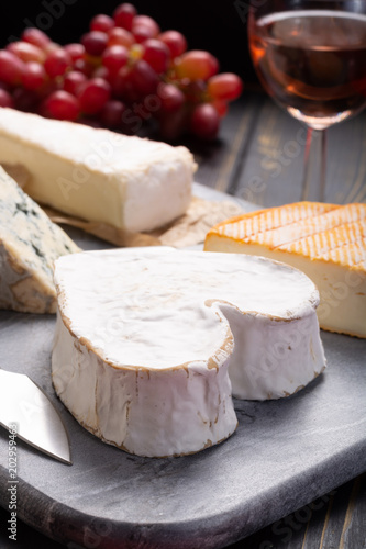 Poster Assortiment French cheeses plate in assortment, Neufchatel heart shaped aged white cow cheese from Normandy