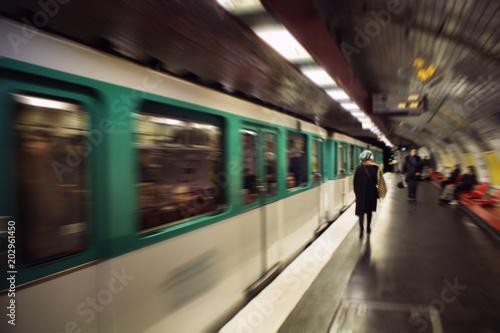 Plakat Rozmazany obraz ruchu kobiety spaceru na stacji metra. Zbliża się pociąg. Koncepcja stylu życia i kultury
