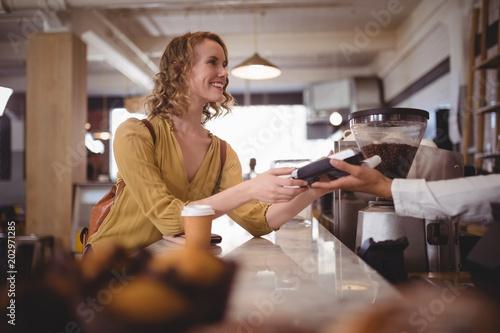 Pinturas sobre lienzo  Smiling beautiful female customer paying through card at counter