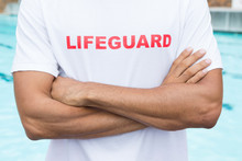 Mid Section Of Lifeguard Standing With Arms Crossed