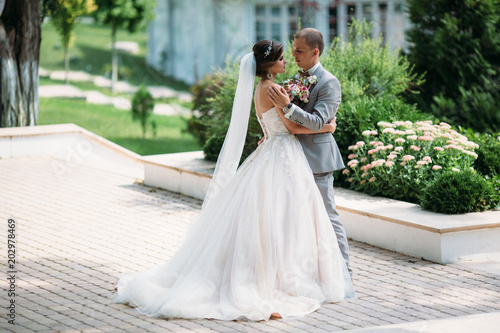 Happy Couple Hugging And Hanging Out In The Park The Bride In A