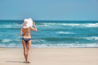 Woman full-length, back view on paradise idealistic beach. White sand, blue sky and crystal sea of tropical beach