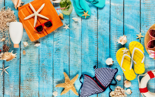 Beach accessories placed on blue wooden planks, top view.